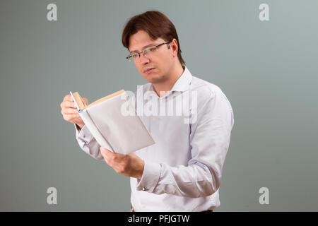 Un jeune homme porté sur la lecture d'un livre à couverture blanche; l'orientation horizontale portrait studio. Banque D'Images