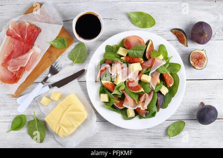 Jeunes épinards frais, figues, émincé de jambon italien et mozzarella Salade fromage tendre sur plaque blanche sur le plan de travail de cuisine en bois avec des ingrédients sur ba Banque D'Images