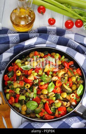 Ragoût épicé avec des légumes, des olives vertes, des câpres, le céleri et les herbes dans une poêle, vertical Vue de dessus Banque D'Images