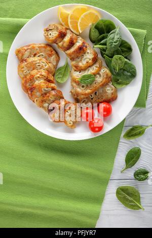 Tranches de salé désossé farci poulet pilons avec des pâtes, de la viande hachée et légumes servi avec bébés épinards, tomates et les tranches de citron sur whit