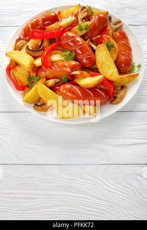 Fun pour de délicieuses saucisses grillées avec des frites, les champignons et le persil sur une assiette blanche sur une table en bois, vue verticale d'en haut Banque D'Images