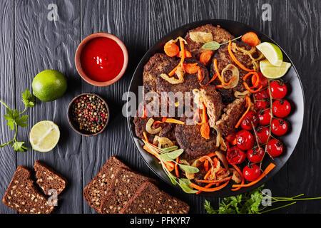 Foie de poulet crêpes avec carotte, oignon servis sur une plaque noire avec des tomates grillées, du ketchup et du pain. lime sur une table en bois, vue horizontale fr Banque D'Images
