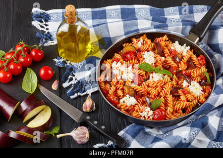 Les pâtes italiennes Les végétariens les fusilli alla Norma avec des aubergines, tomates, basilic, fromage ricotta et sauce marinara dans une poêle avec des ingrédients au bac Banque D'Images
