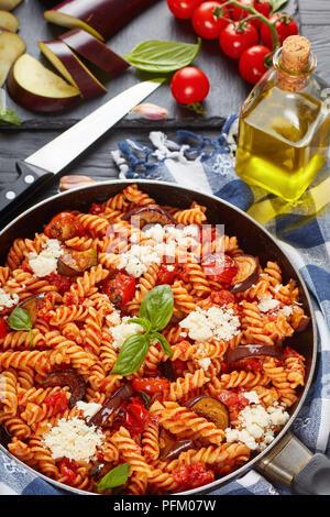 Les pâtes italiennes Les végétariens les fusilli alla Norma avec des aubergines, tomates, basilic, de ricotta dans une poêle avec des ingrédients à l'arrière-plan, vertical v Banque D'Images