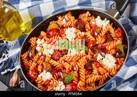 Les pâtes italiennes Les fusilli alla Norma avec des aubergines, tomates, basilic, de ricotta dans une poêle avec des ingrédients à l'arrière-plan, Vue de dessus, le clos Banque D'Images