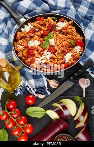 Les pâtes italiennes Les végétariens les fusilli alla Norma avec des aubergines, tomates, basilic, de ricotta dans une poêle sur une table en bois avec des ingrédients à l'arrière Banque D'Images