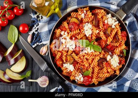 Les pâtes italiennes Les fusilli alla Norma avec des aubergines, tomates, basilic, de ricotta dans une poêle sur une table en bois avec des ingrédients à l'arrière-plan, ver Banque D'Images