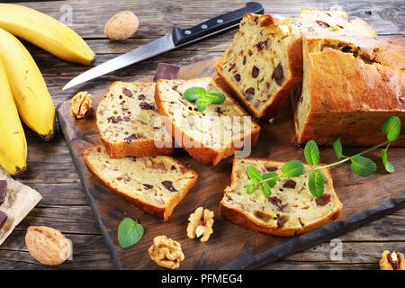 Des délicieux pain à la banane avec des noix et des morceaux de chocolat coupé en tranches sur une planche à découper. Ingrédients sur une table en bois rustique, american cu Banque D'Images