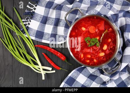 Soupe rouge betterave délicieux avec des haricots blancs ou bortsch dans une casserole en acier inoxydable avec serviette, piment et oignon de printemps sur la table, authentique destinat Banque D'Images