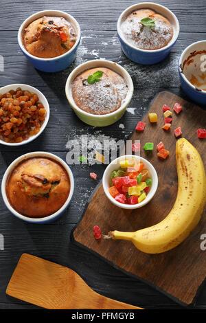 Délicieux faits maison fraîchement préparés Bananes et noix et raisins Muffins dans des ramequins en céramique saupoudrée de sucre en poudre sur une table en bois noir avec des ingrédients à