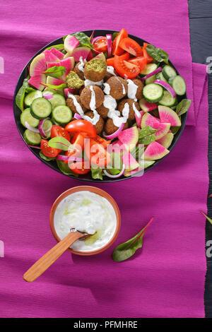 Boules de falafel délicieux sur la plaque avec légumes salade colorée de melon radis, concombre, feuilles de bette à carde et de tranches de tomate. sauce tzatziki dans bol,
