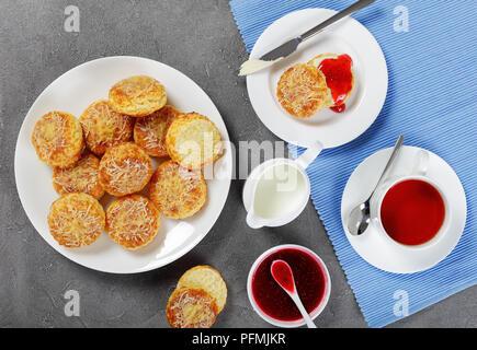 Petit-déjeuner anglais - tasse de thé servi avec du lait et verseuse délicieux scones anglais fraîchement cuits au four avec du beurre et de la confiture de framboise, vue d'en haut Banque D'Images
