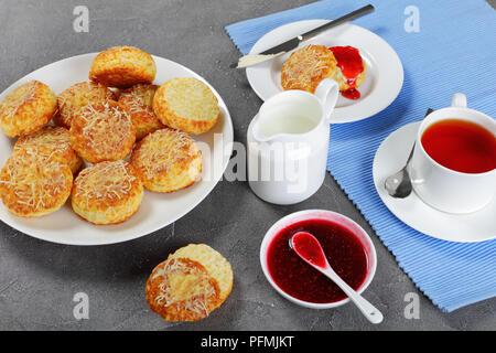 Petit-déjeuner anglais - tasse de thé servi avec du lait et verseuse délicieux scones anglais fraîchement cuits au four avec du beurre et de la confiture de framboise, vue de dessus, le clos Banque D'Images