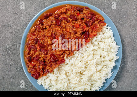 Close-up of sex délicieux chili con carne avec des haricots rouges, la viande bovine la farcissure prг©parent et épices servi sur une assiette avec du riz bouilli sur table béton classique, Banque D'Images
