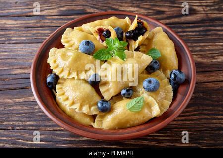 Boulettes de bleuets, pierogi, vareniki dans une cuvette d'argile sur une vieille table de cuisine, vue de dessus, close-up Banque D'Images