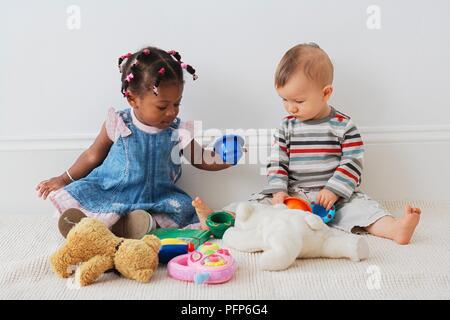 13 mois et 10 mois bébé fille garçon bébé assis sur le sol en jouant avec des jouets Banque D'Images