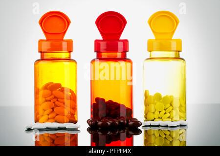 Comprimés de vitamine à l'intérieur et à l'avant de bouteilles de pilules Banque D'Images