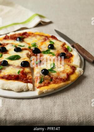 Pizza sans gluten avec les olives et le basilic, la seule tranche découpée Banque D'Images