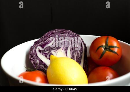 Le chou rouge coupé en deux dans un bol blanc avec du citron et tomate isol Banque D'Images