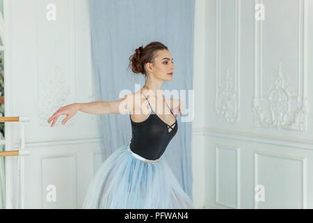 Jeune danseuse de ballet classique vue de côté. Belle ballerine ballet gracieux pratique des positions en tutu jupe près de grand miroir dans la salle de lumière blanche. B Banque D'Images