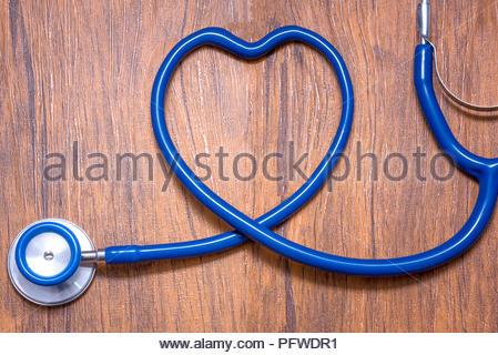 Stéthoscope bleu en forme de coeur sur fond d'un bureau en bois. Banque D'Images