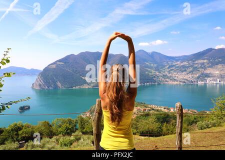 Heureux attractive young woman in sportswear bénéficiant d'étirement paysage Lac Iseo dans la matinée, au nord de l'Italie. L'humeur joyeuse, émotions vraies, santé Banque D'Images