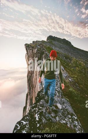 Homme marchant seul sur le bord de la crête de montagne au-dessus des nuages voyage d'aventure extrême de vie vacances de randonnée Banque D'Images