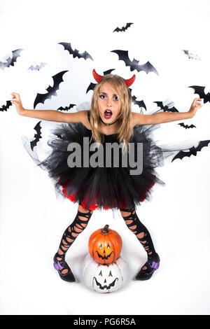 Petite fille avec un démon costume habillé en noir robe rouge et red devil horns pour citrouille et Halloween Party, qui posent avec plaisir smi Banque D'Images