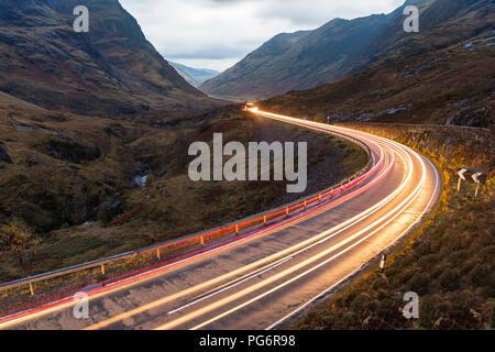 Royaume-uni, Ecosse, location light trails sur scenic route à travers les montagnes dans les highlands écossais près de Glencoe au crépuscule Banque D'Images