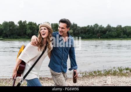 Heureux couple en train de marcher au bord du fleuve avec une bouteille de bière et la guitare Banque D'Images