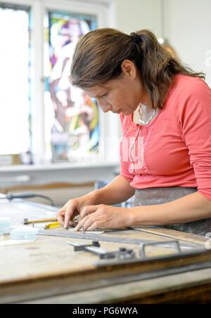 Femme travaillant au poste de travail en atelier vitrier Banque D'Images