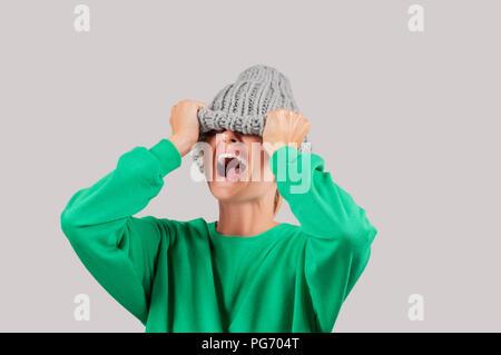 Furieux. Femme en colère émotionnelle est tirant sur ses yeux chapeau en laine sur fond gris Banque D'Images
