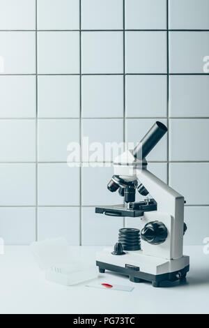 Échantillon de sang et d'un microscope optique sur tablette blanc en face de mur carrelé Banque D'Images