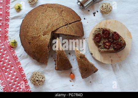 Pain frais et tomates séchées sur nappe rustique blanc