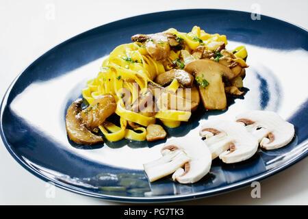 En forme de ruban: tagliatelles de pâtes fraîches faites maison habillé avec un ragoût de champignons. Banque D'Images
