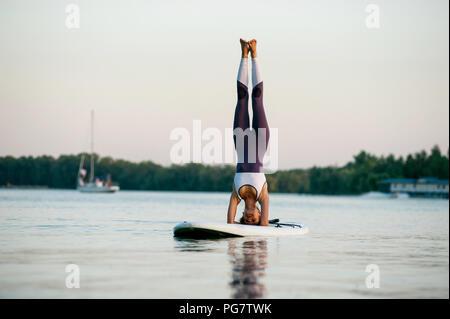 Stand Up Paddle board yoga effectué par belle fille sur la ville, l'arrière-plan lumineux fille se tient sur la tête. Banque D'Images