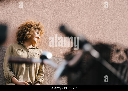 Laughing woman in front of house wall, profiter du soleil