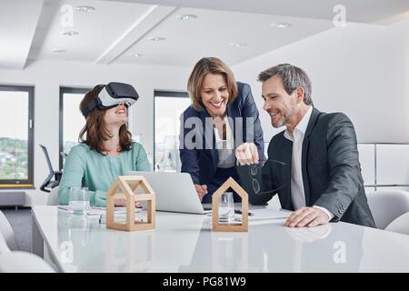 Les gens d'affaires ayant une réunion en bureau avec ordinateur portable, lunettes VR et maquettes d'architecture Banque D'Images