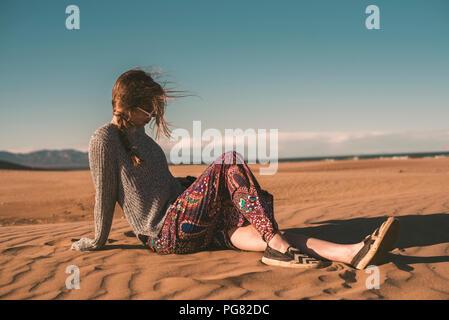 L'Espagne, fashinable jeune femme assise sur la plage Banque D'Images