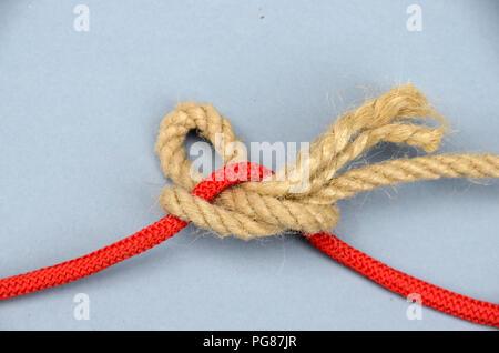 L'attelage rapide avec la corde de chanvre sur corde en nylon rouge. Banque D'Images