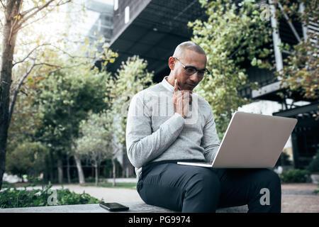 Businessman working on laptop computer assis à l'extérieur avec un téléphone mobile à ses côtés. La gestion des travaux de l'entrepreneur d'affaires assis à l'extérieur. Banque D'Images
