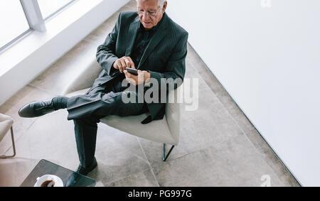 High angle view of senior businessman texting avec téléphone mobile. Professionnel à la maturité de la lecture de courriers électroniques sur son smartphone pendant les pauses. M Senior Banque D'Images