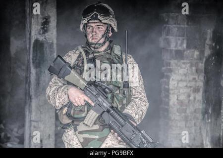 Soldat des forces spéciales, commando Marine Corps fantassin, fighter dans casque et l'armure de corps, équipée de radio tactique, armés de fusil de service avec l'op Banque D'Images