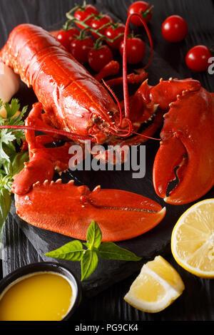 Délicieux homard bouilli libre avec citron, tomates fraîches et d'herbes sur un fond noir. vertical Banque D'Images