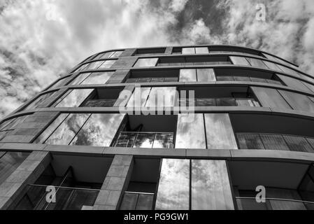 Bâtiment de verre réfléchissant la lumière en noir et blanc Banque D'Images