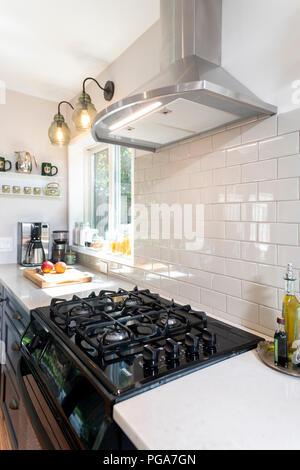 Une cuisinière à gaz dans une maison moderne équipée avec une hotte électrique avec un dosseret de carreaux blancs Banque D'Images