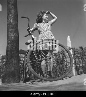 1940 fille avec location. Une jeune fille, habillée d'une robe à carreaux, est debout près de son vélo d'une journée ensoleillée. La Suède Mai 1940. 133-2 Kristoffersson Photo Banque D'Images