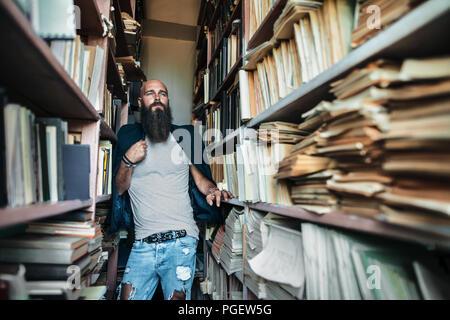 Portrait d'homme barbu hippie chic in library