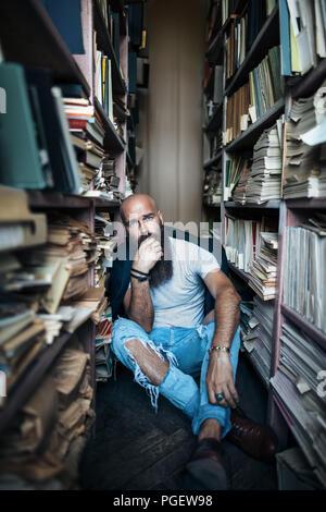 Hipster bouleversé man sitting on floor in library concept de dépression.
