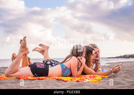 L'été, vacances, congés, de la technologie et de bonheur concept - group of smiling people with sunglasses taking picture with smartphone sur plage. happin Banque D'Images
